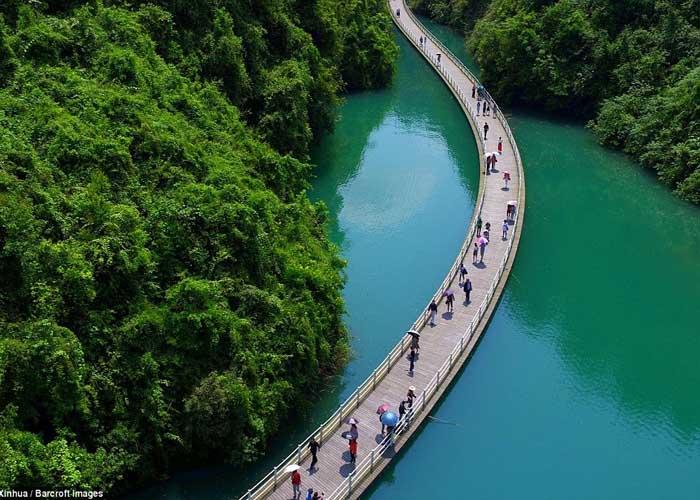 Keskeny híd kanyarog hosszában egy folyó közepén
